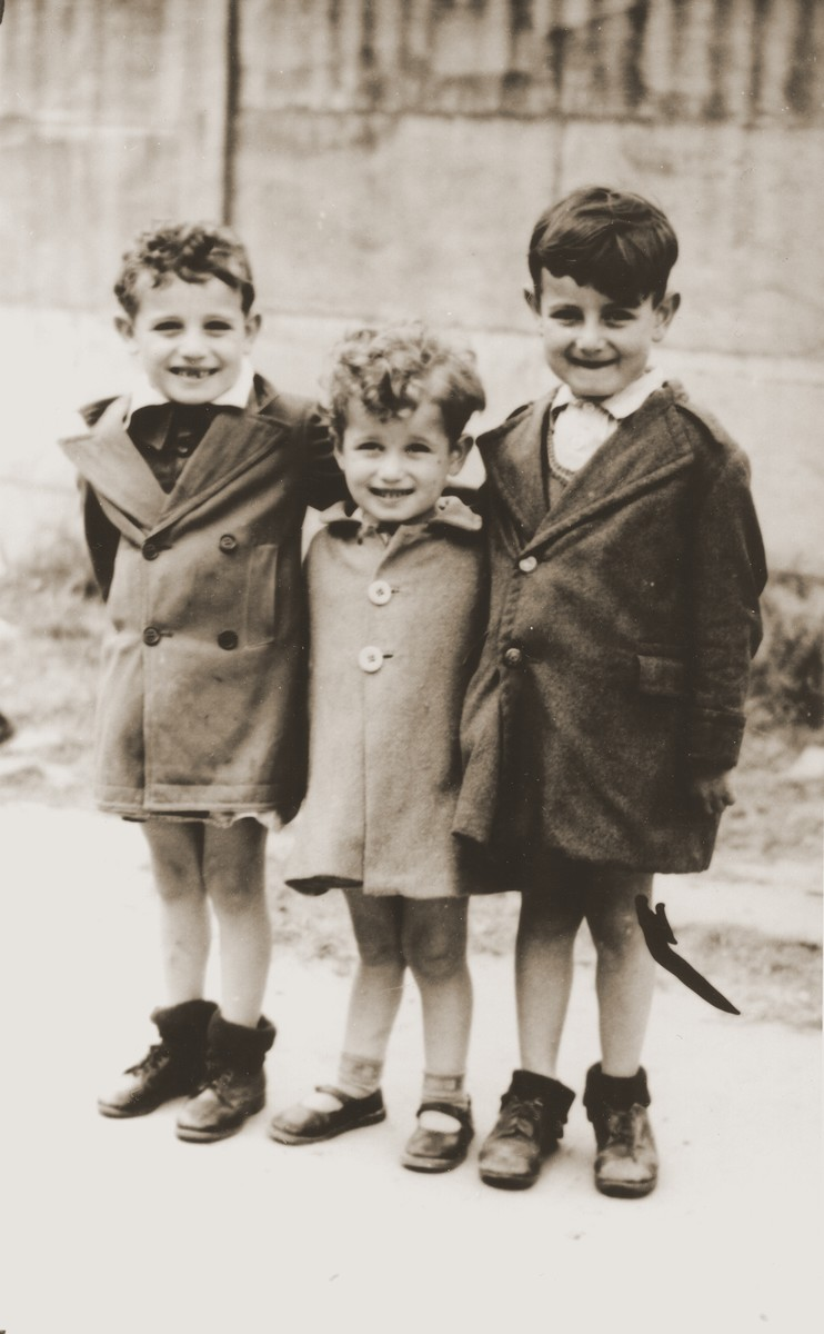 Three young children pose outside the La Pouponniere children's home in Uccle.