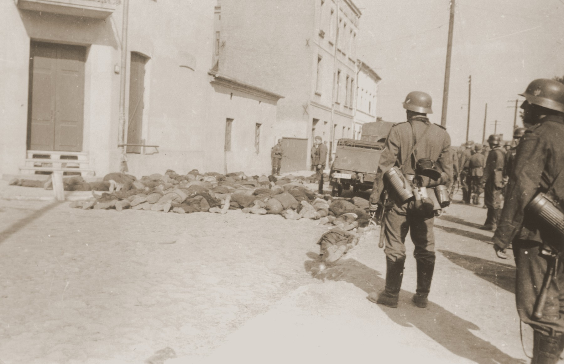 German soldiers stand guard on a street in Czestochowa, where the bodies of Jewish men they have shot lie on the pavement.  One photograph from an album belonging to a member of a Wehrmacht machine gunners' unit, which was found after the war by Lorenzo Hawkins (the donor's grandfather), an American serviceman in Company B, 56th Armored Engineer Battalion.