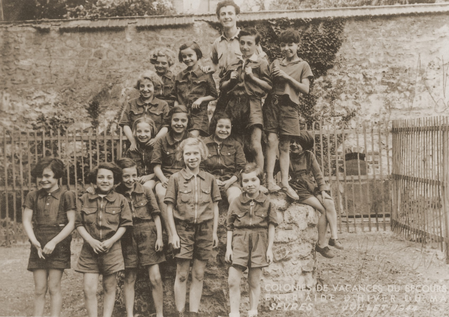 Group portrait of Jewish children in the yard of the Les Bruyeres children's home in Sevres.  OSE successfully hid some thirty Jewish children in this Vichy children's home.    Marcel Mengel (now Marcel Marceau) is standing at the top.