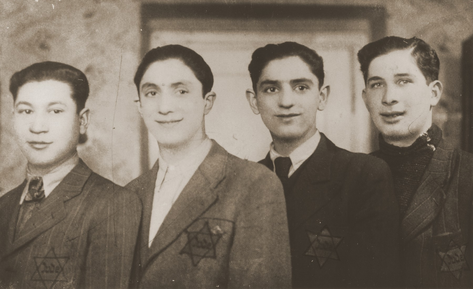 Four teenage boys wearing Jewish badges in Sosnowiec.  Pictured are David and Aaron Jakobowicz (center) with two friends.
