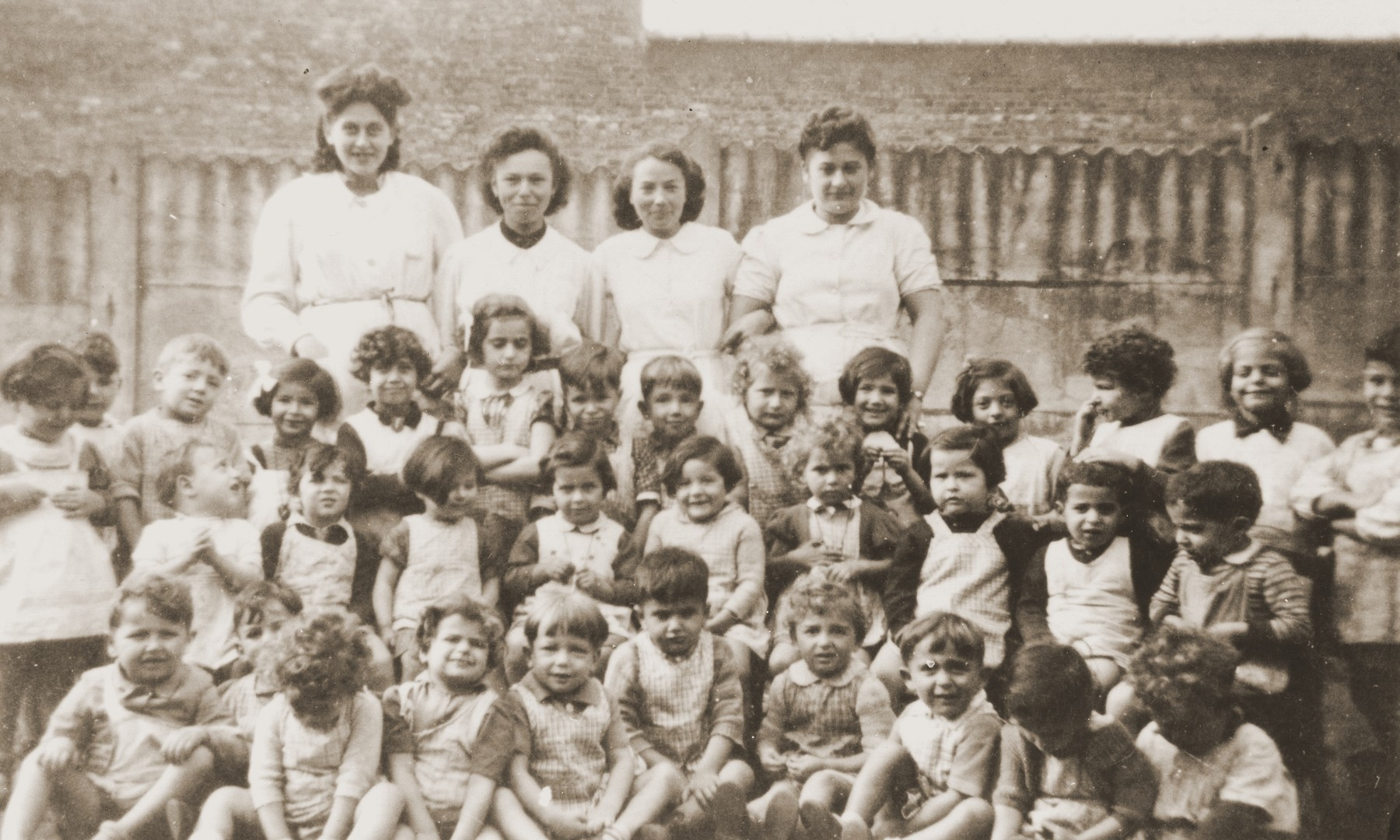 Group portrait of the children and staff of La Pouponniere children's home in Uccle.  Among those pictured are Paula Bucholc, Jeannette, and DeeDee (second row, 4th, 3rd, and 2nd from the right).