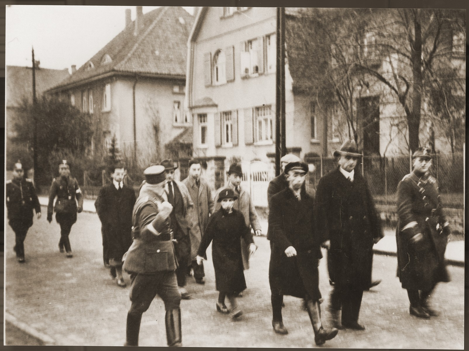 A small group of Jews, who have been rounded-up for arrest after Kristallnacht, is escorted down a street by German police, SA and SS members.