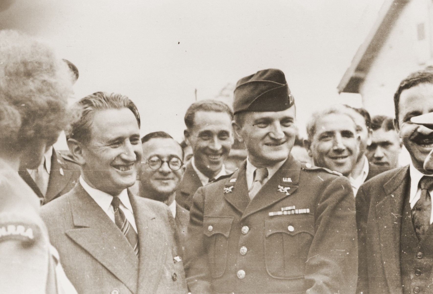 Nahum Goldmann, chairman of the executive council of the World Jewish Congress, is escorted through the Lampertheim displaced persons camp by Captain Abraham Hyman (center in uniform) and Mathilde Oftedal (left).