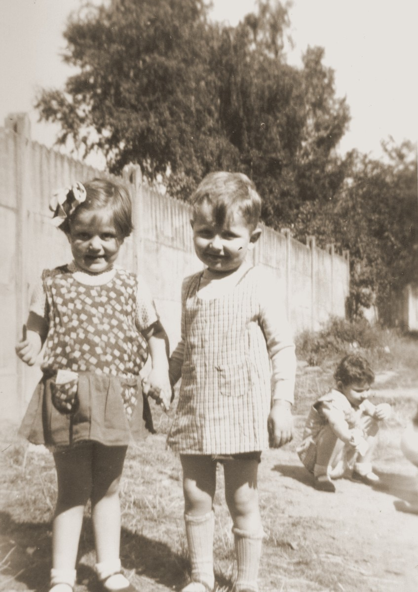 A young boy and girl pose in the yard of the La Pouponniere children's home in Uccle.