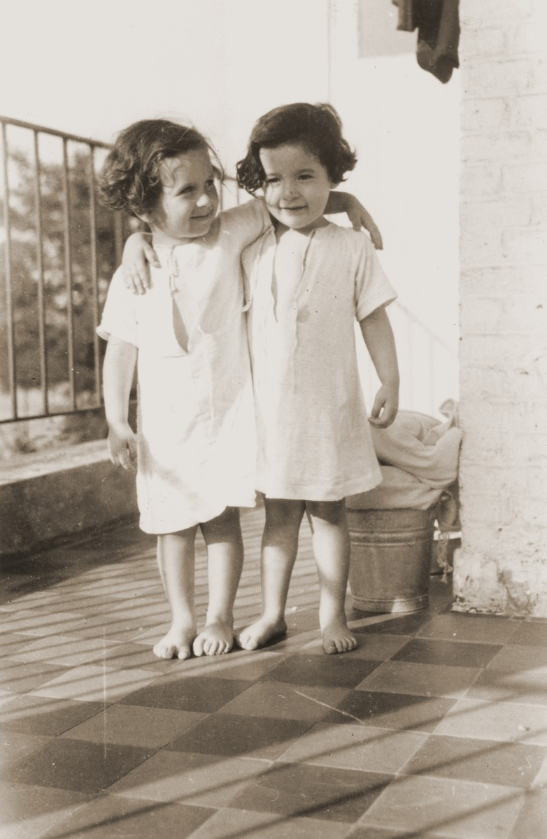 Two young girls stand on the porch of La Pouponniere children's home in Uccle.