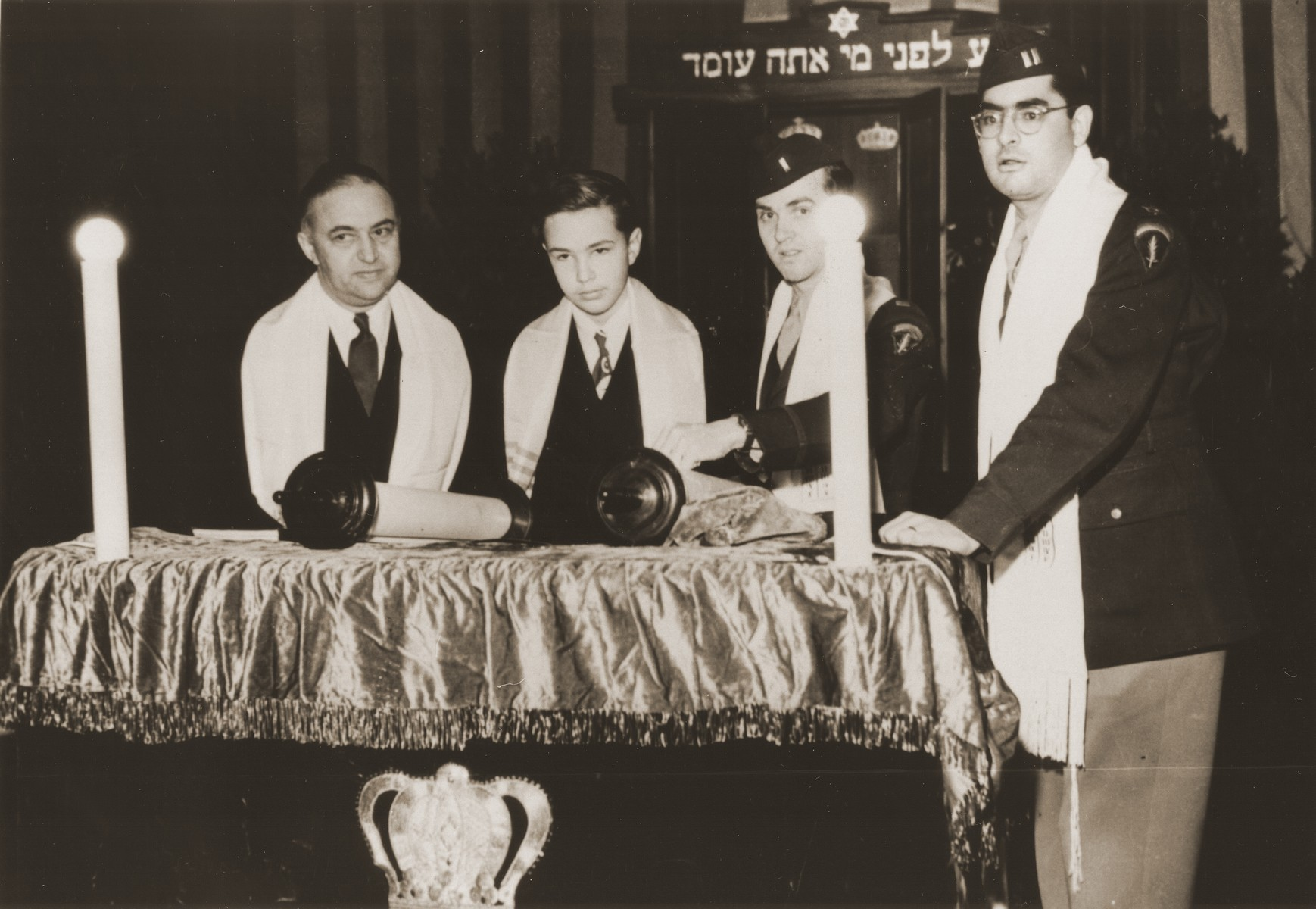 Stephen Bernstein, son of American chaplain Philip Bernstein, reads from the torah at his bar mitzvah at the Philanthropin School in Frankfurt, Germany.  Pictured from left to right are Rabbi Philip Bernstein, Stephen Bernstein, Rabbi Mayer Abramowitz, and Rabbi Herbert Friedman.