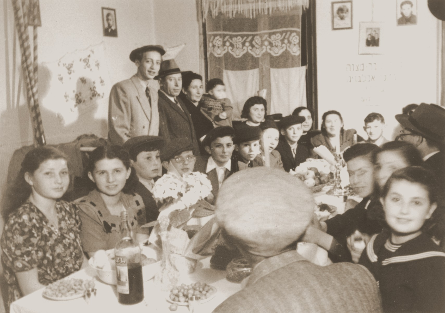 "Motel (Mordechai) Appelbaum (sitting beneath a sign) celebrates his Bar Mitzvah with family and friends in the Gabersee displaced persons camp.  The Hebrew sign reads, ""Bar Mitzvah party of Mordechai Appelbaum...[illegible]""."
