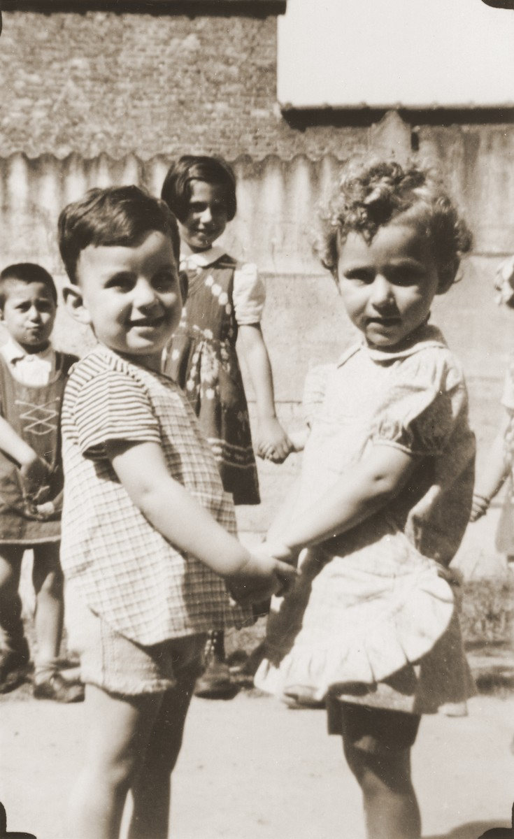 Two young children hold hands in the yard of the La Pouponniere children's home in Uccle.  Among those pictured is Paula Bucholc (right).