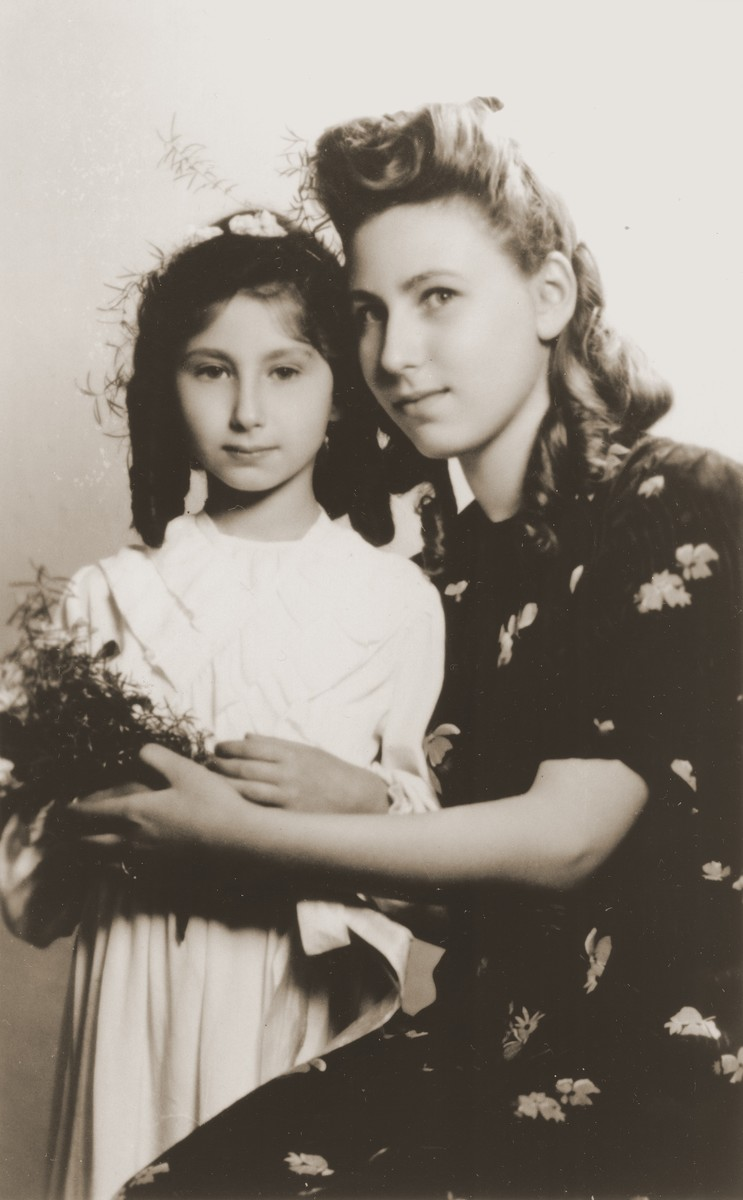 Two Jewish sisters who are living in hiding in Warsaw, pose for a formal portrait at the time of the younger girl's First Communion.  Pictured are Alicja Fajnsztejn (right) and Zofja Fajnsztejn (left).