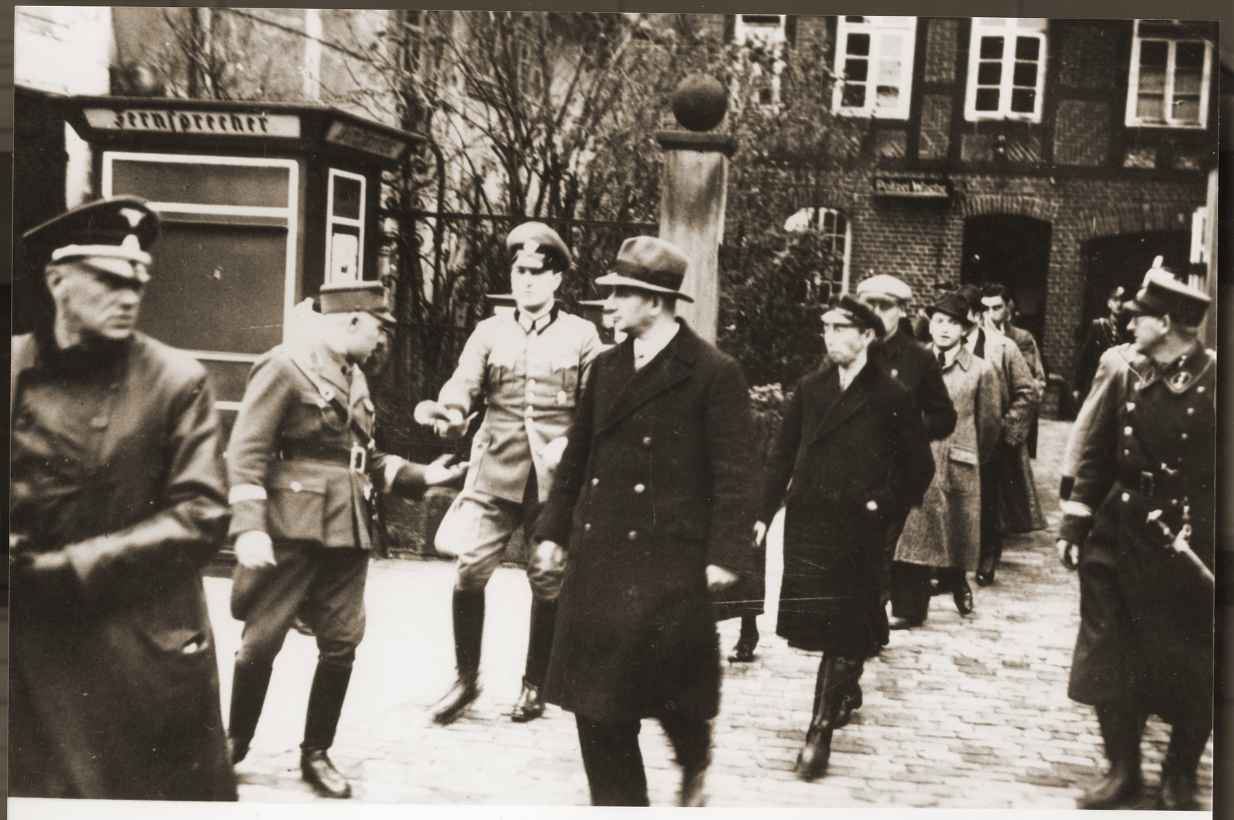 A small group of Jewish men, who have been rounded-up for arrest in the days after Kristallnacht, file out of the police station in Stadthagen, escorted by German police and SA members.