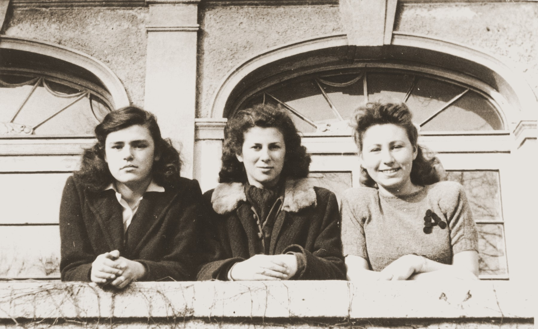 Alicja Fajnsztejn (right) poses with two friends on a balcony of a building in the Foehrenwald displaced persons camp.  Halina Bentley is in the center.