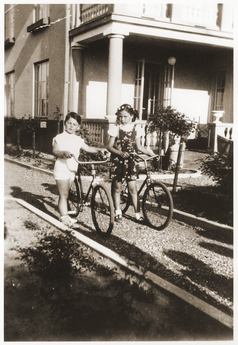 Alicja Fajnsztejn and her cousin Ryszyard ride their bicycles in front of their summer home in Mlociny, outside of Warsaw.
