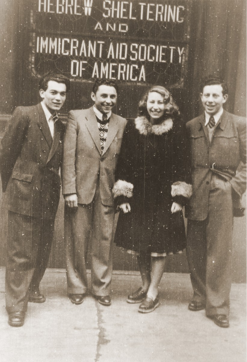 Alicja Fajnsztejn poses with friends from the Foehrenwald displaced persons camp in front of a HIAS sign in the port of New York after her arrival aboard the SS Marine Jumper.
