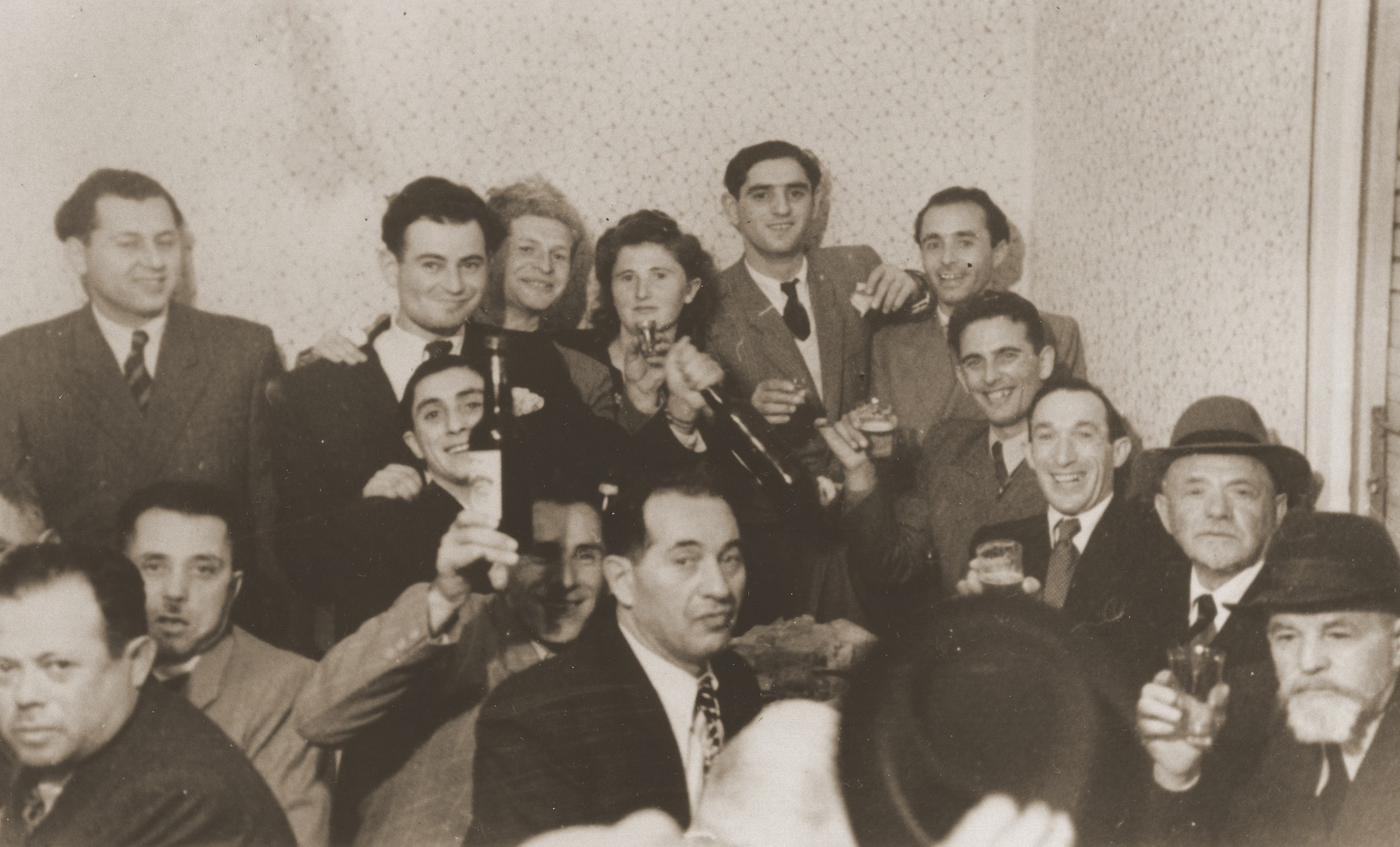 Jews raise their glasses and wine bottles in a toast at a social gathering in Sosnowiec.  Among those pictured are David and Hanka Enzelewicz, and David, Aaron and Joseph Jakobowicz.