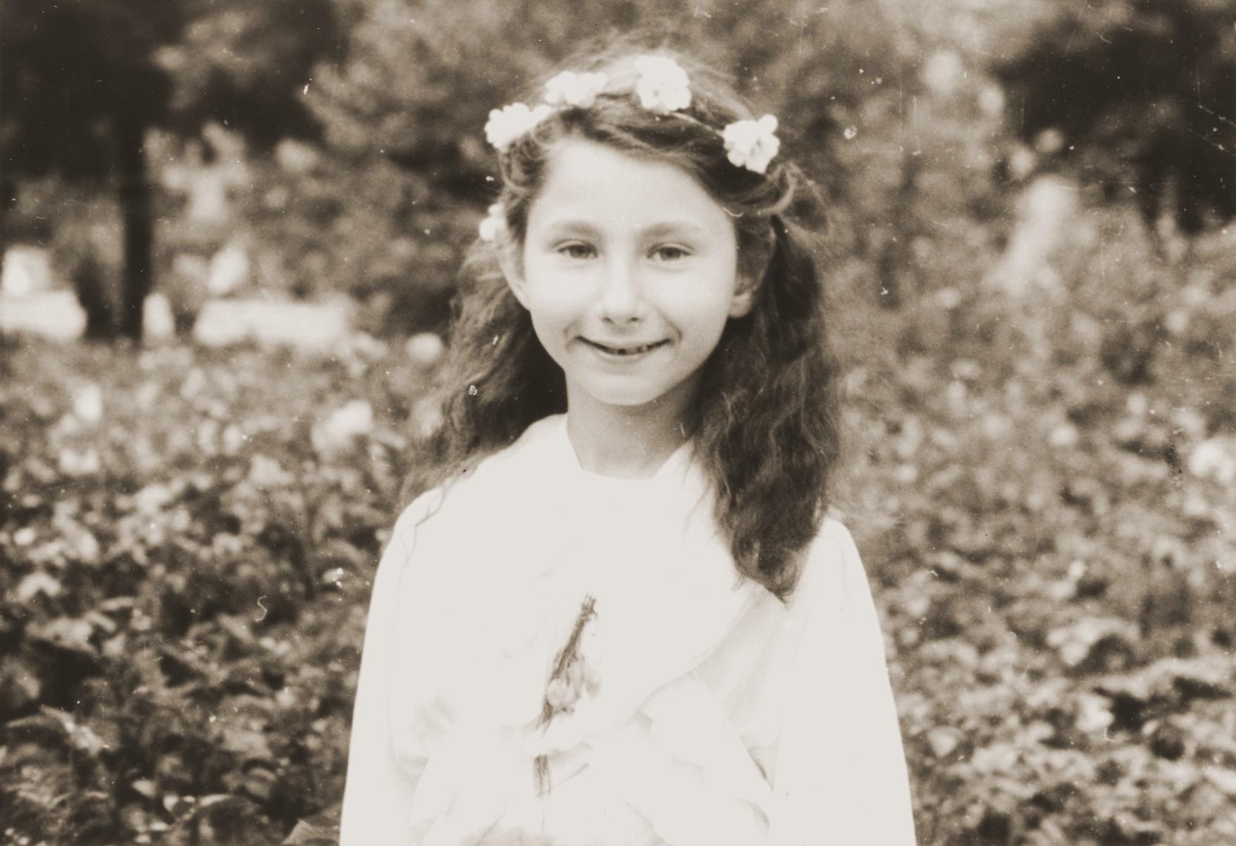 Zofja Fajnsztejn, a Jewish child in hiding, poses outside in a garden wearing her First Communion dress.