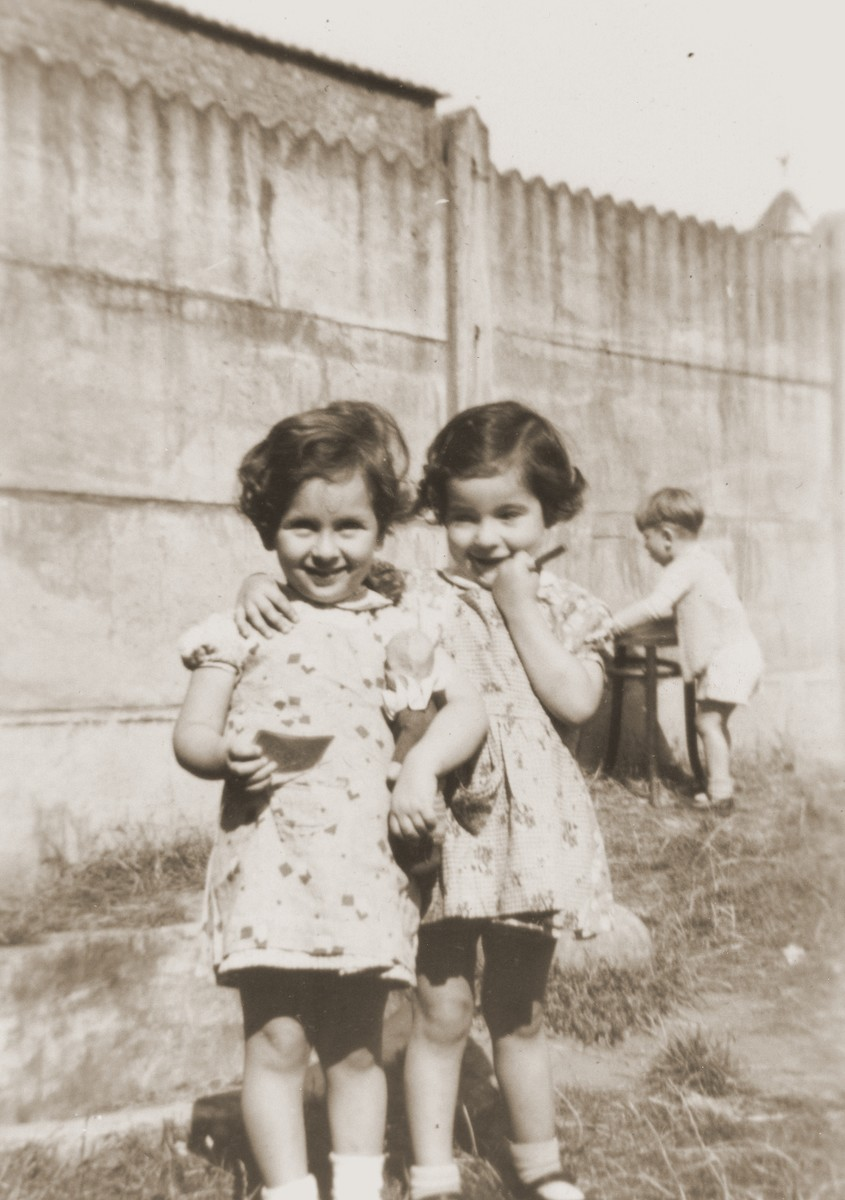 Two young girls pose in the yard of the La Pouponniere children's home in Uccle.