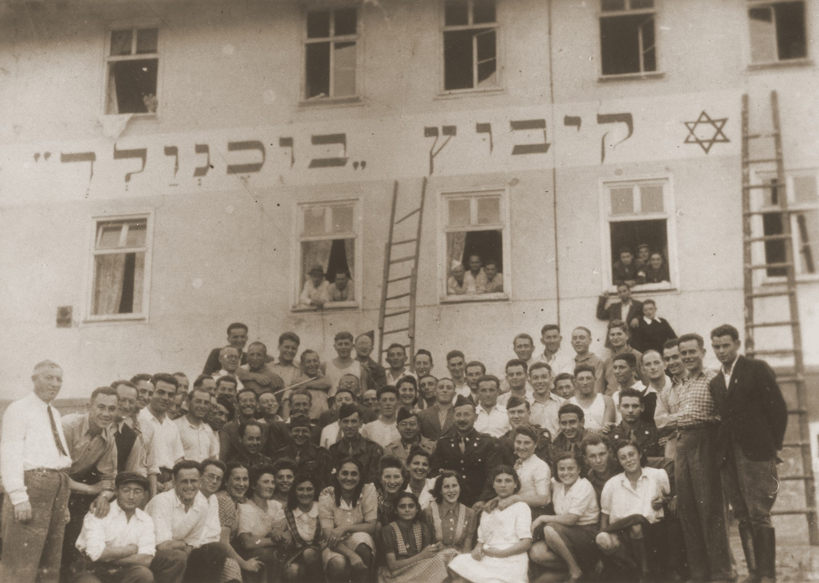 Members of the Kibbutz Buchenwald hachshara are gathered outside their barracks, beneath a banner bearing their name in Hebrew.