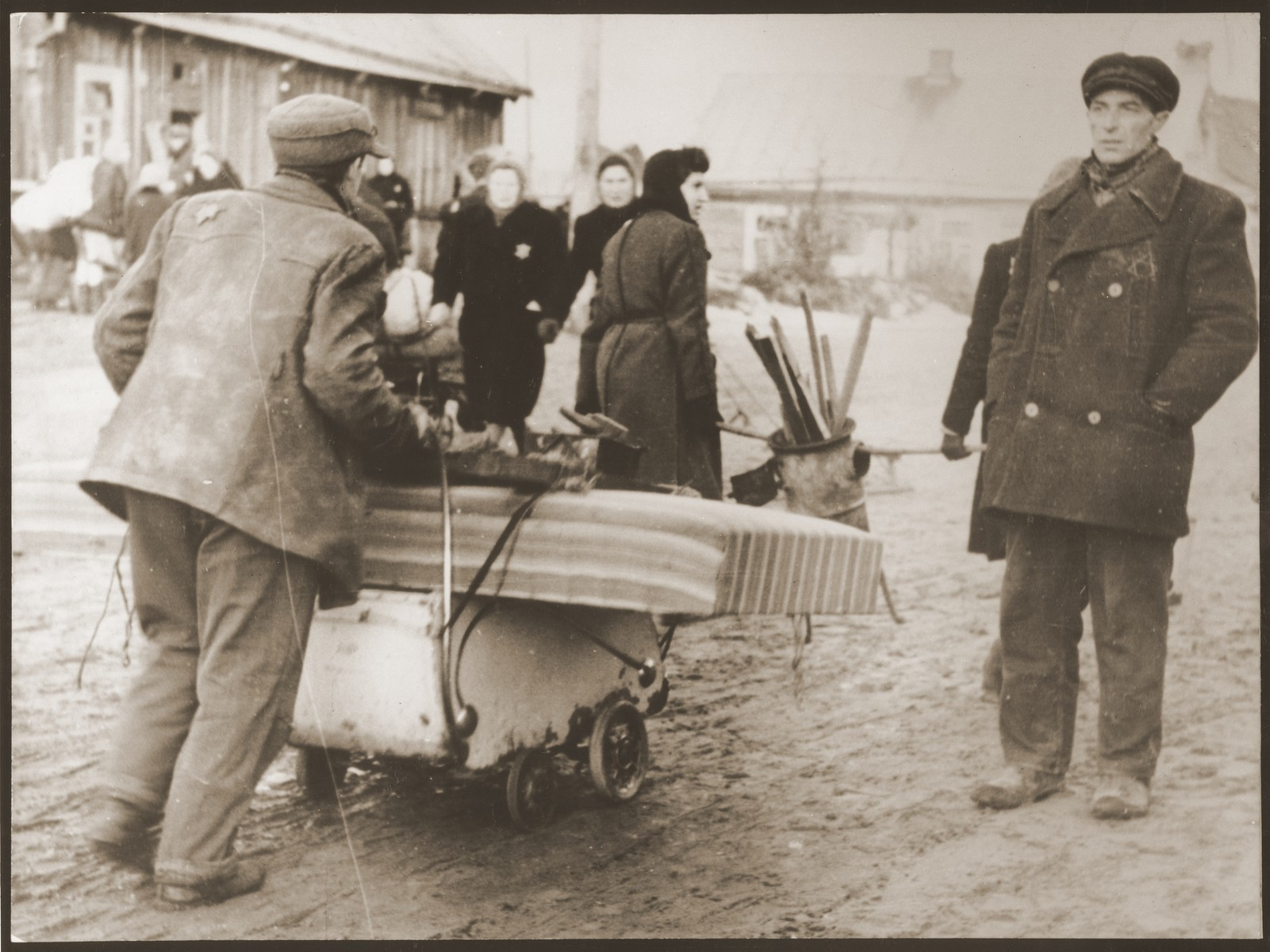 Residents of the ghetto move to new housing after the Germans reduced the borders of the Kovno ghetto.  Since there were no vehicles, these residents are using a baby carriage to transport their belongings.