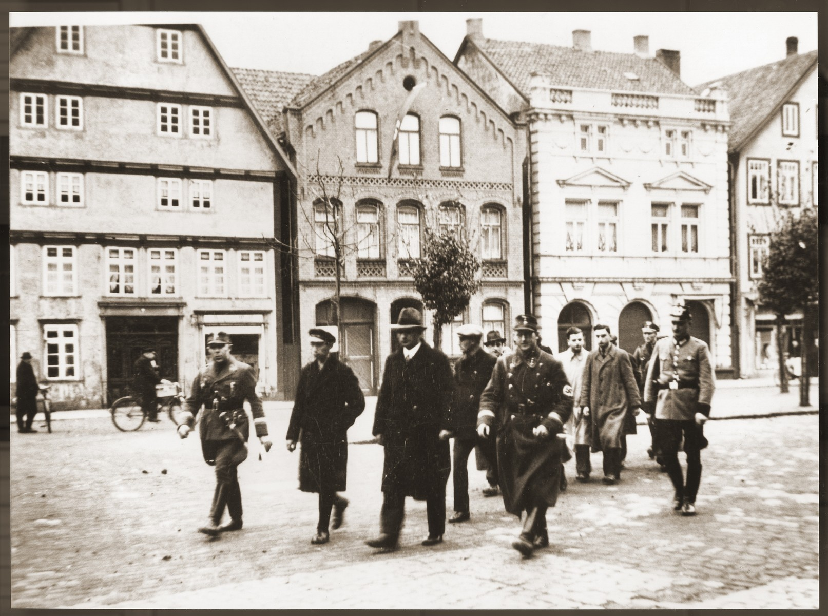 A small group of Jewish men, who have been rounded-up for arrest in the days after Kristallnacht, is escorted down a street by German police and SA members.