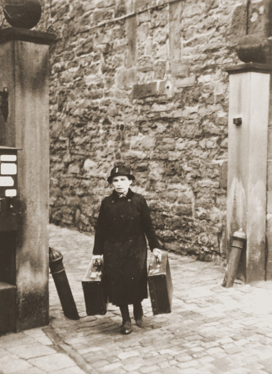 A  woman carrying two suitcases leaves her home during a round-up of local Jews for arrest in the days after Kristallnacht.