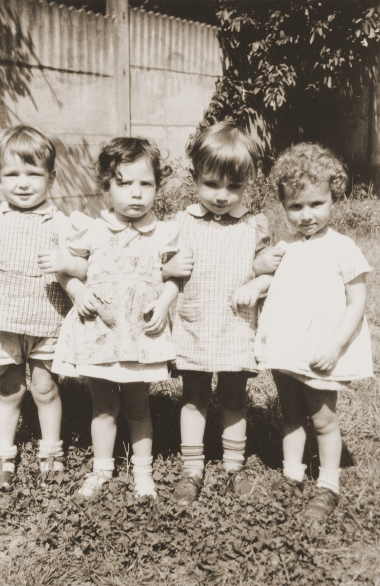 Four small children pose in the yard of the La Pouponniere children's home in Uccle.  Among those pictured is Paula Bucholc (far right).