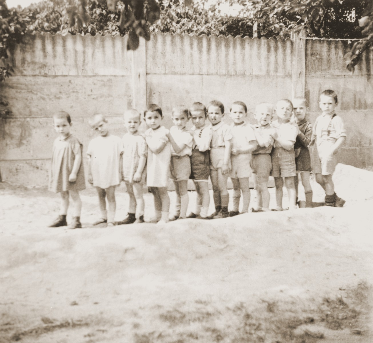 A group of toddlers form a line in the yard of the La Pouponniere children's home in Belgium.