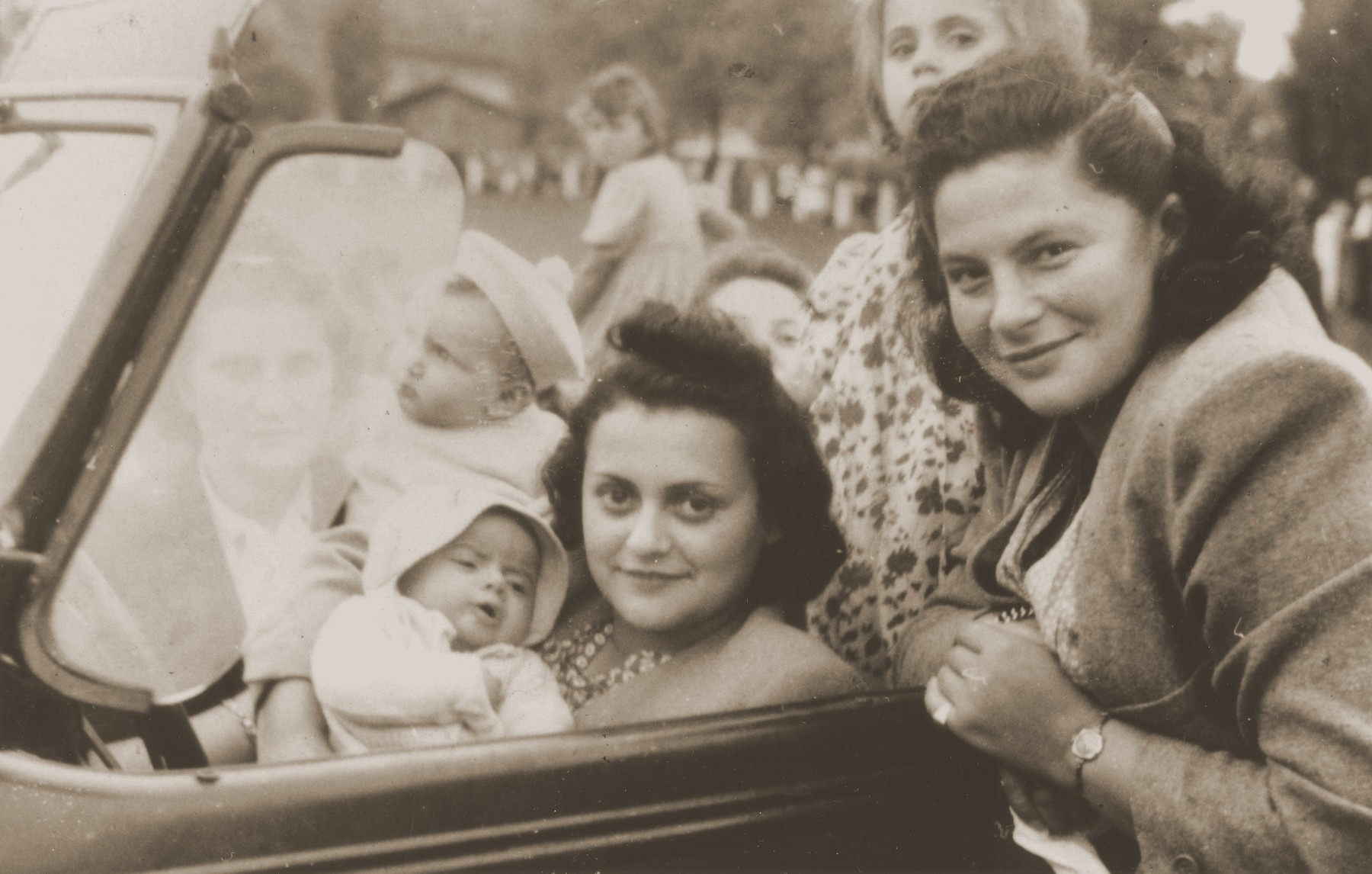 Jewish friends pose in a car while on an outing with their children in Sosnowiec.