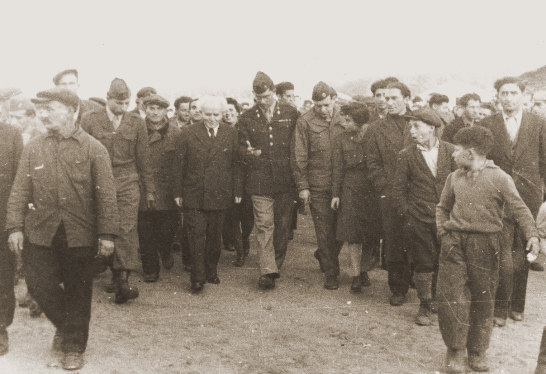 Rabbi Herbert Friedman escorts Zionist leader David Ben-Gurion through a crowd of admirers in the Babenhausen DP camp.