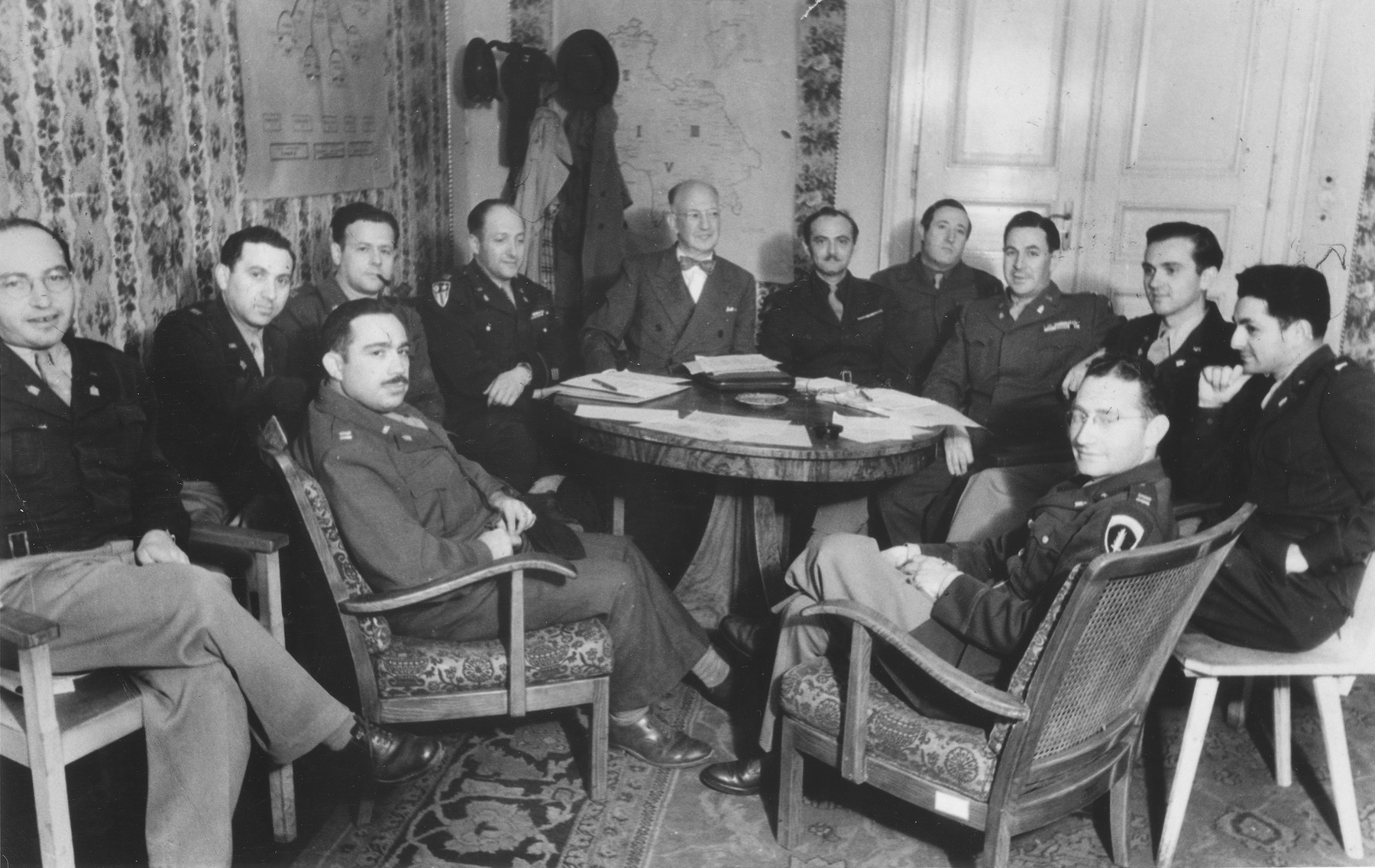 American Jewish army chaplains attend a meeting called by Judge Louis Levinthal, Advisor on Jewish Affairs to the U.S. Army in Germany.    Among those pictured are Judge Louis Levinthal (with bow tie); Mayer Abramowitz (second from the right, in front of the door); Abraham Klausner (far right); and Oscar Lifschutz (front left in the arm chair).