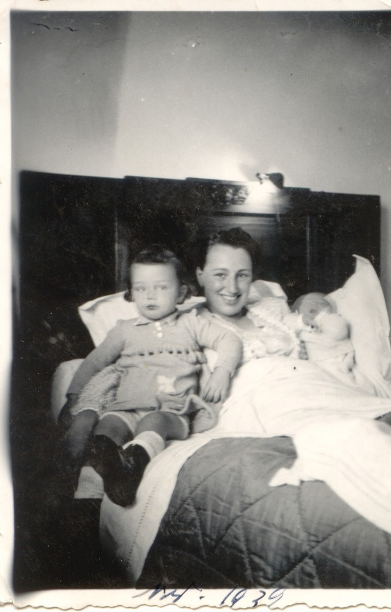 Germaine Brunschwig holds her newborn daughter Sylvie in her arms while her older daughter Arlette sits on the side of the bed.