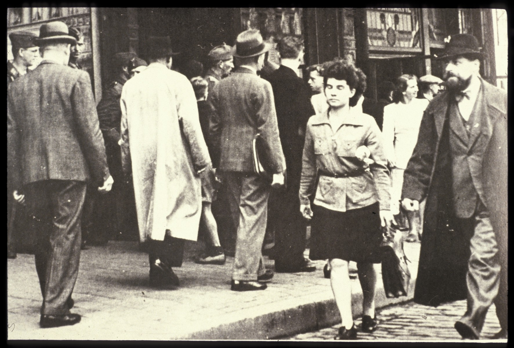 """[Belgian] Jews are forced to walk in the street.  The original photo caption reads, """"Jews in gutter."""""""