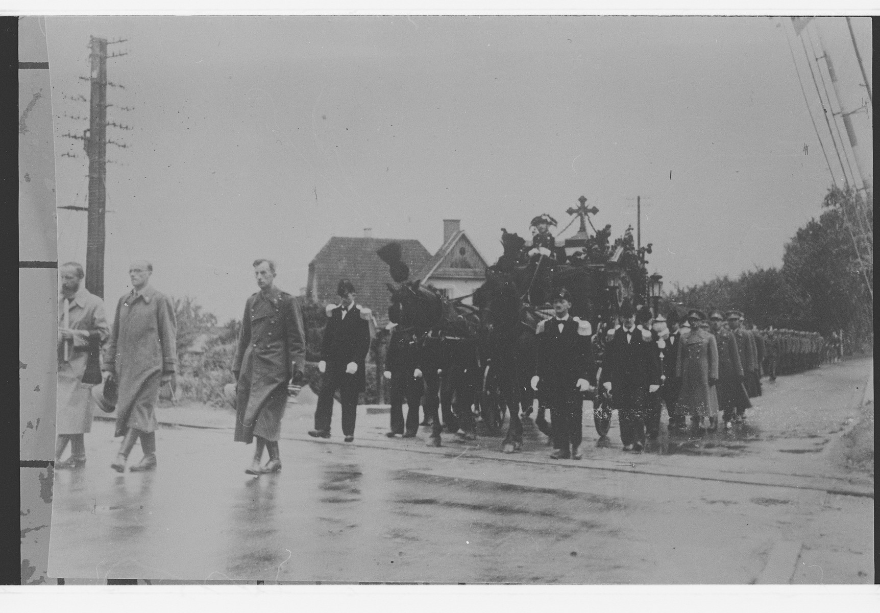 Father Bruno (Henri Reynders) leads a military funeral procession while serving as a chaplain in a prisoner of war camp.
