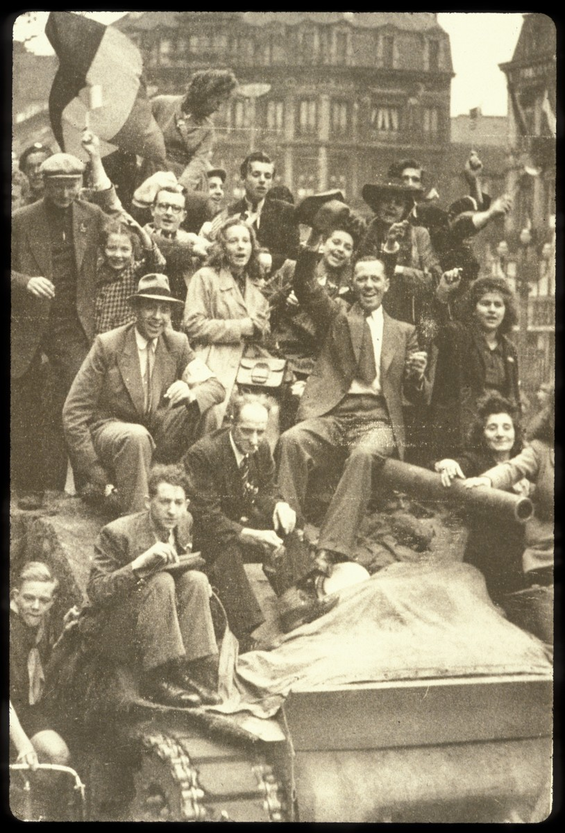 Jubilant Belgians sit on top of a tank and celebrate the liberation of Brussels.