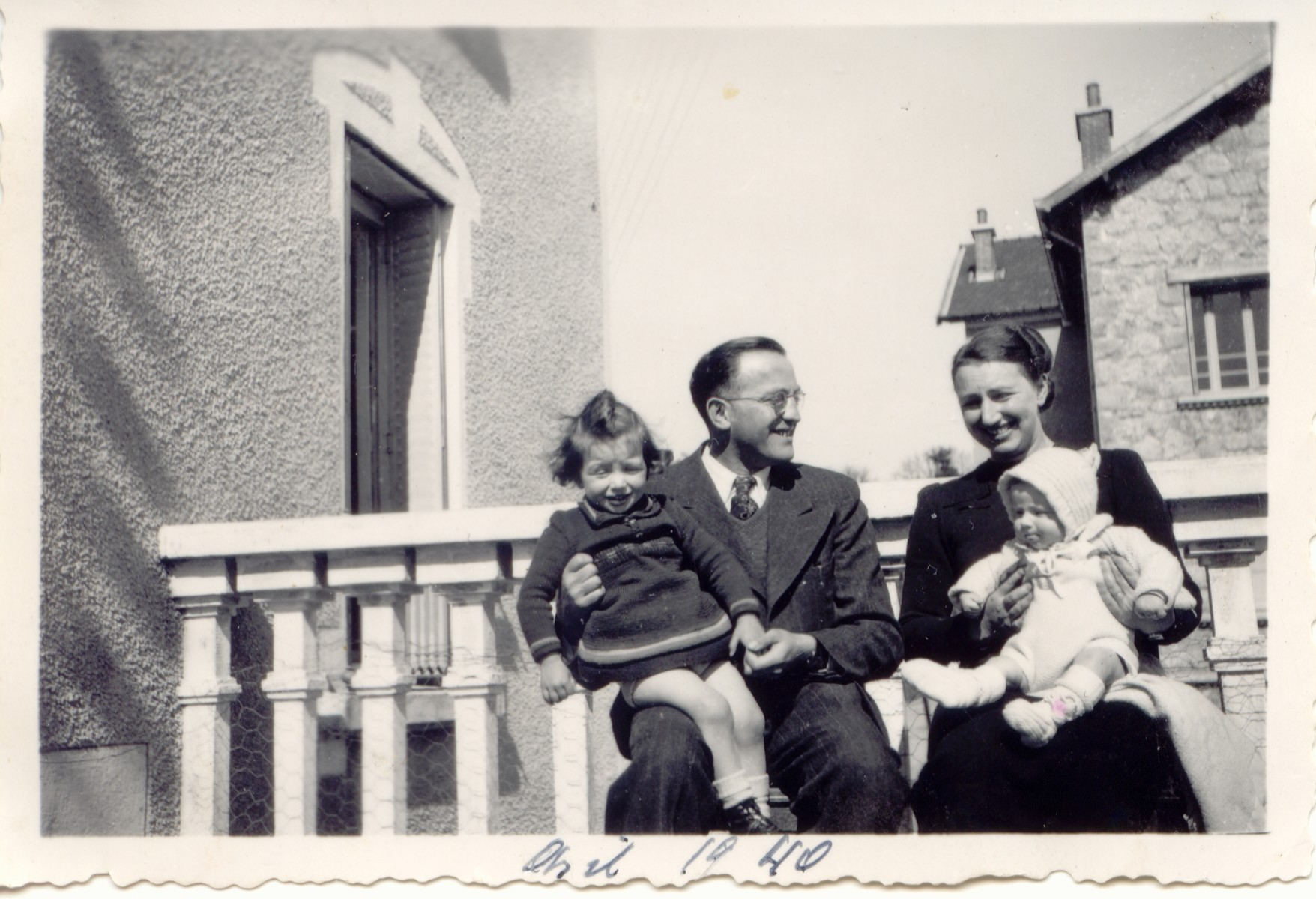 Rene and Germaine Brunschwig pose on a balcony holding their two young daughters, Arlette and Silvie, on their laps.