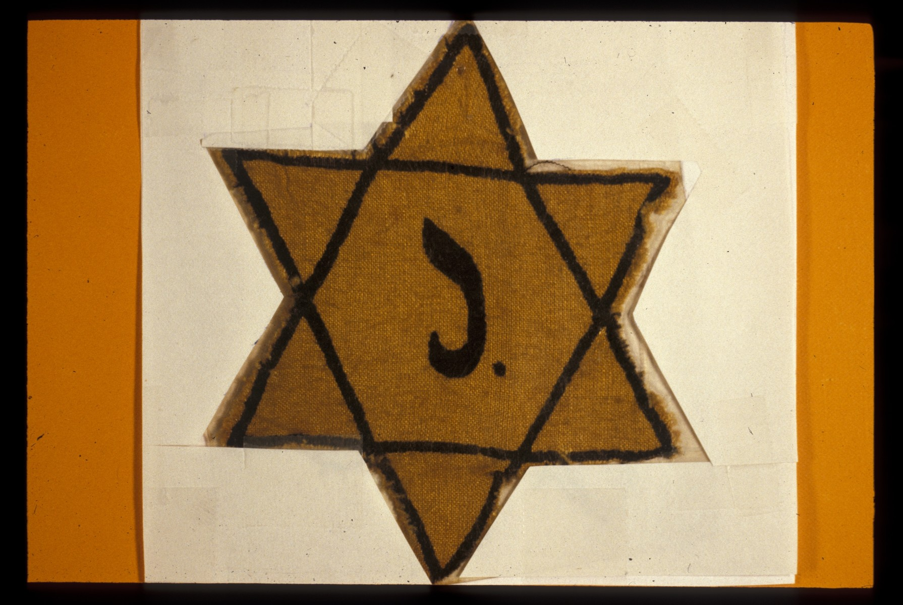 A cloth Star of David stamped with a J for Juif.
