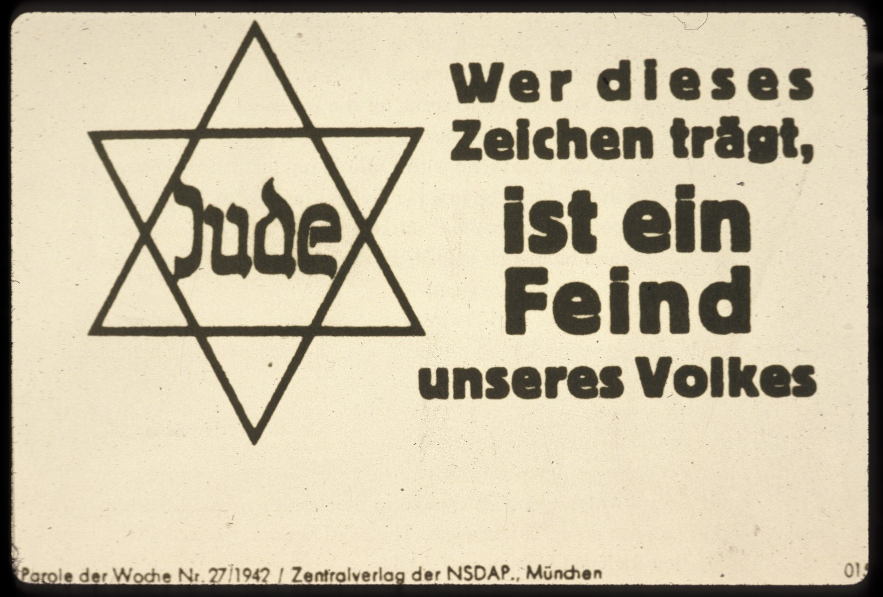 """Nazi propaganda poster with a picture of a Jewish star and a German caption that reads, """"Whoever wears this symbol is an enemy of our Volk."""""""