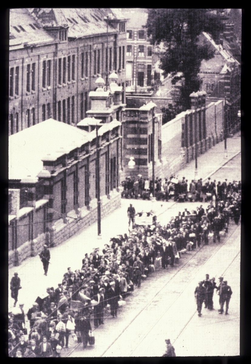 A large crowd of Jews marches down a street after their round-up in Brussels.
