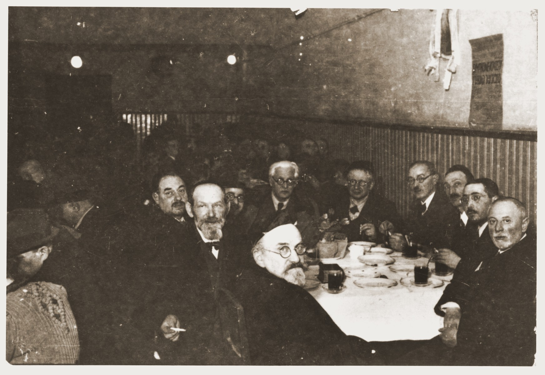Mordechai Chaim Rumkowski, chairman of the Jewish council, meets with a group of rabbis around a table in a dining hall in the Lodz ghetto.