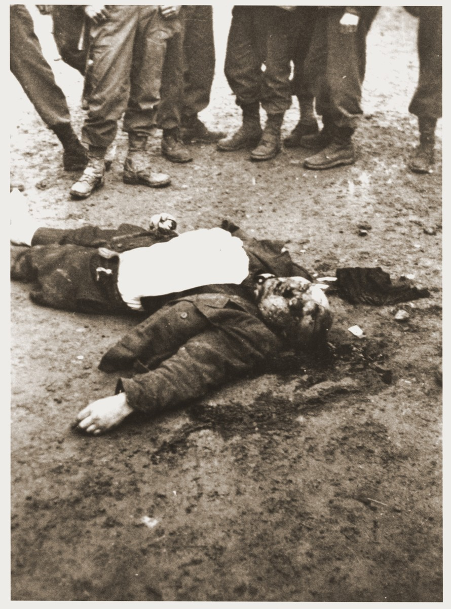 American soldiers view the body of a concentration camp guard killed during the liberation of Ohrdruf.  The photographer served with the 69th Infantry Division during the liberation of Ohrdruf.