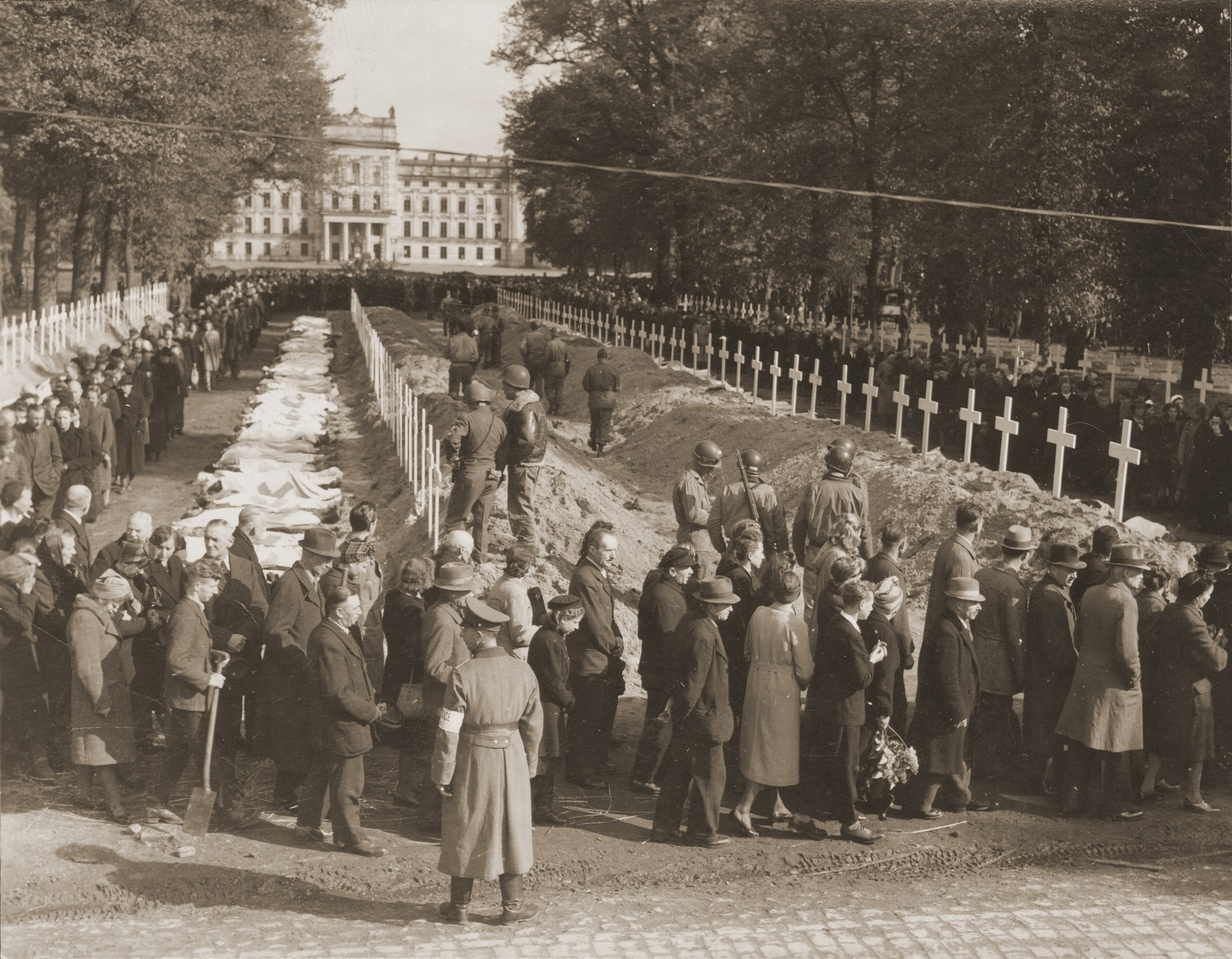 German civilians from Ludwigslust file past the corpses and graves of 200 prisoners from the nearby concentration camp of Woebbelin.  The townspeople were forced by U.S. troops to bury the corpses on the palace grounds of the Archduke of Mecklenburg.  A sub-camp of Neuengamme, Woebbelin was captured by British and American troops on 4 May 1945.  Upon entering the camp, the liberators discovered nearly 4,000 prisoners, one-quarter of whom were already dead.  Outraged by what they found, the ranking Allied commanders in the area forced civilians from the nearby towns of Schwerin, Hagenow, and Ludwigslust to first see Woebbelin and then bury the bodies of prisoners in their towns.  The largest number of bodies, ca. 200, was buried in Ludwigslust on the palace grounds of the Archduke of Mecklenburg.  A slightly smaller number was buried in the garden of the leading Nazi official in Hagenow and 80 bodies were interred in Schwerin.  Every fourth grave was marked at each site with a Star of David in honor of the unidentified Jewish dead.