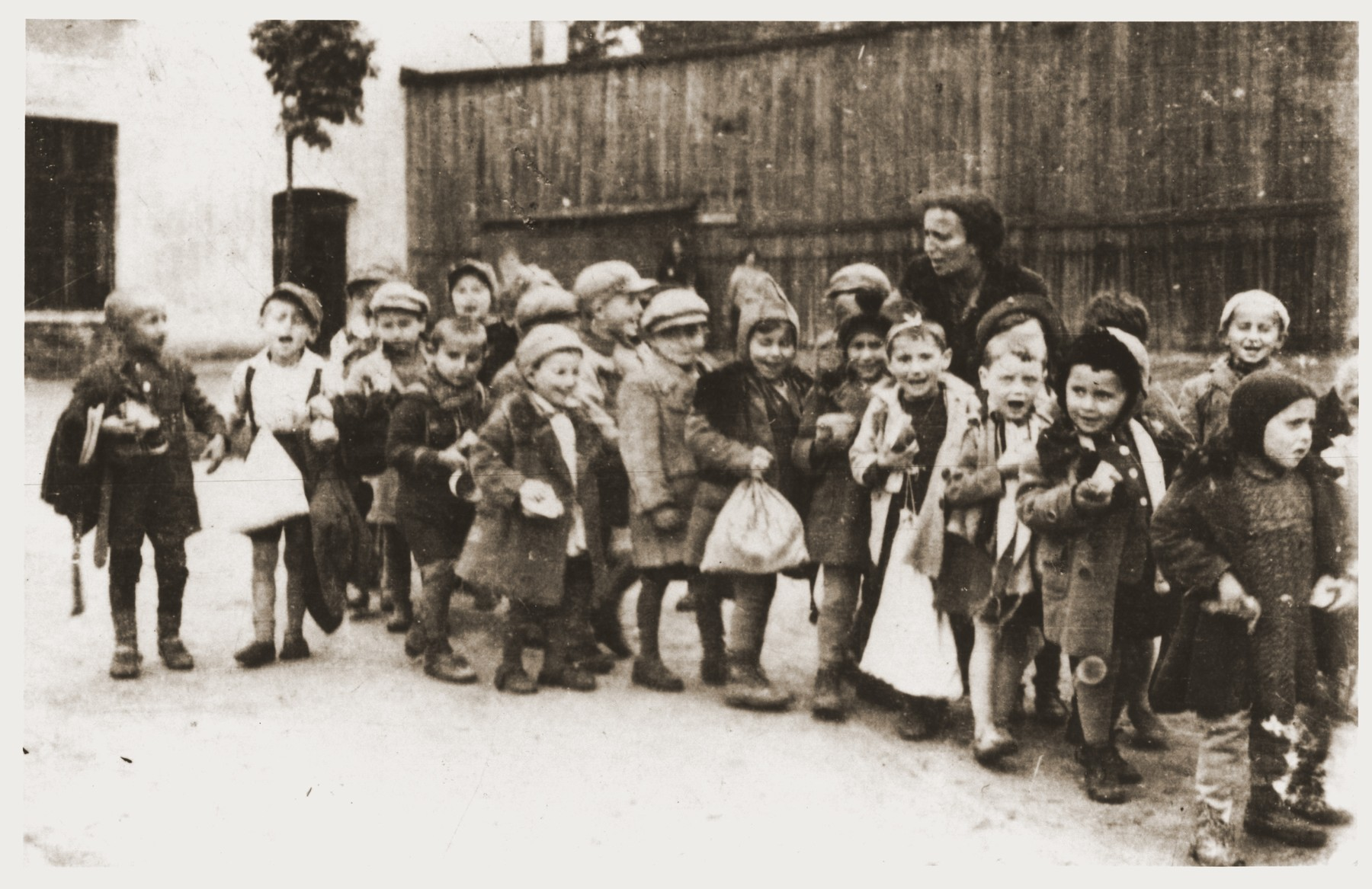 A group of pre-school children lined up with sacks in the Lodz ghetto.