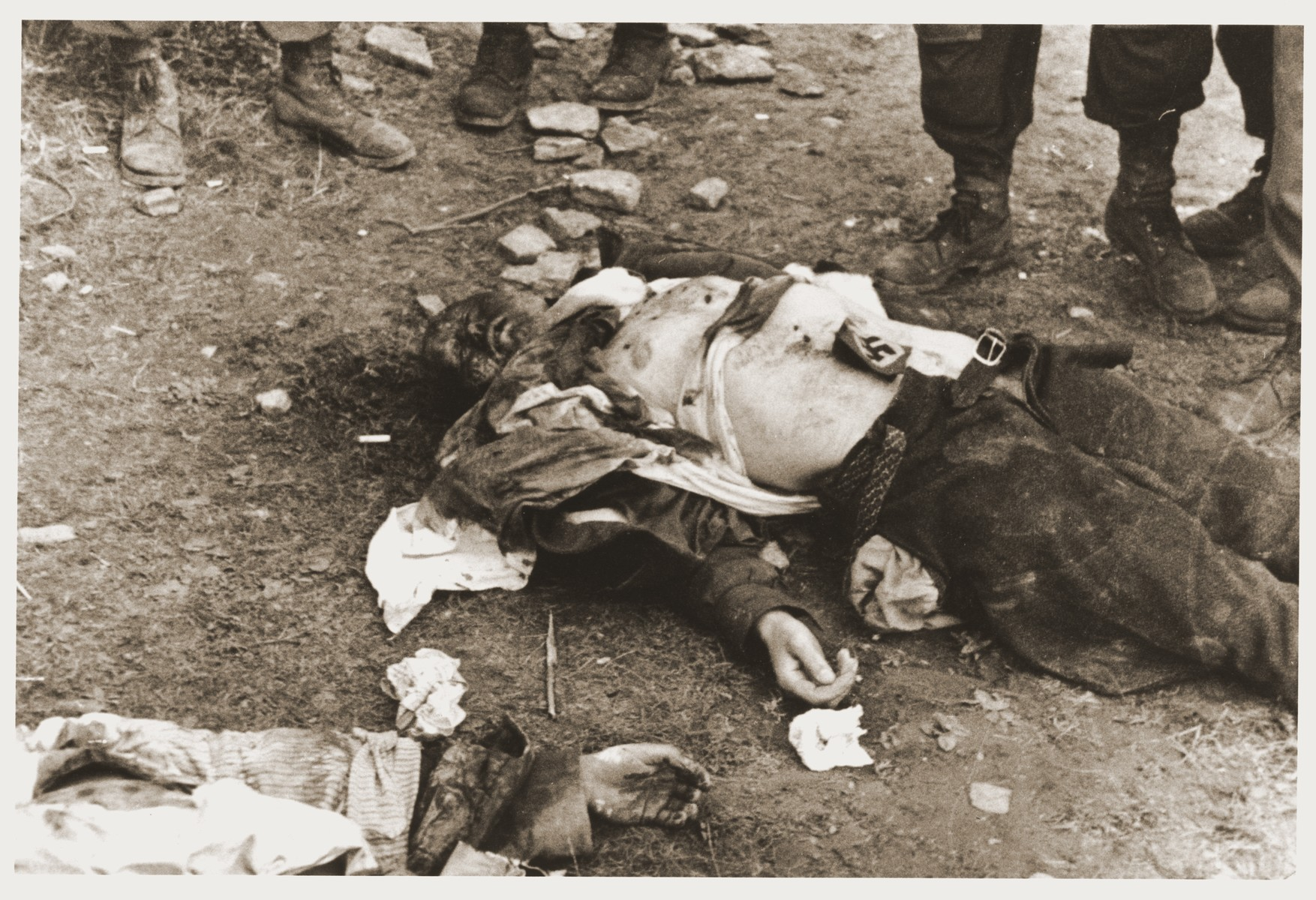 The corpse of a German guard with a swastika on his chest, who was killed by inmates during the liberation of Ohrdruf.    The photographer was an American soldier serving in the 69th Infantry Division, which participated in the liberation of Ohrdruf.