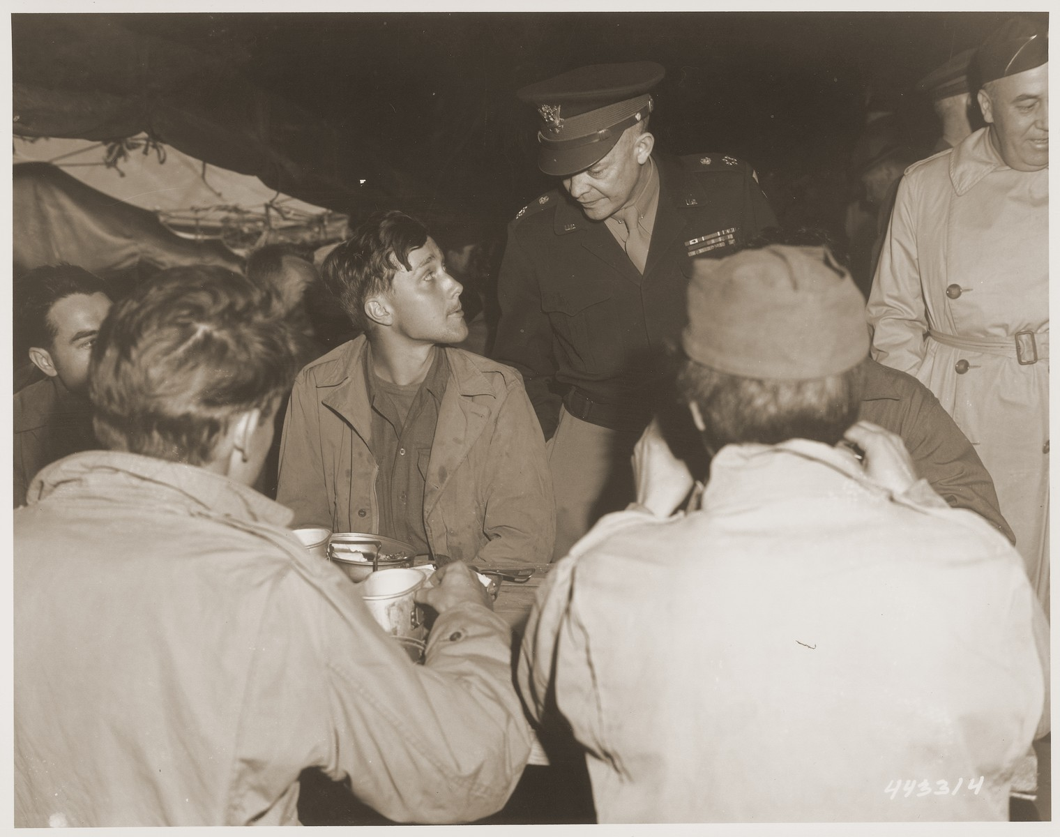 General Eisenhower pauses to speak to Private John D. Hesling of Northeast, Pennsylvania, one of forty thousand American soldiers who became prisoners of war of the Germans.  He is now in a camp in France awaiting transportation to the United States.