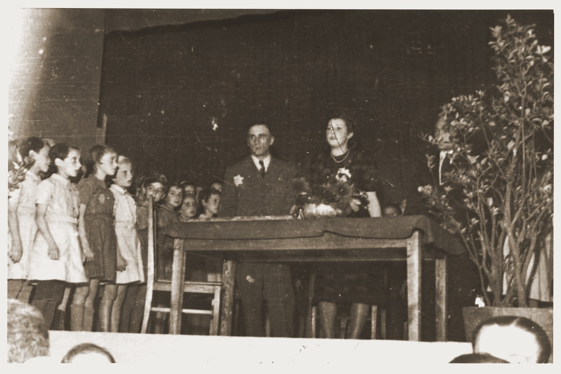 A group of school children are lined up on a stage during a formal presentation in the Lodz ghetto.