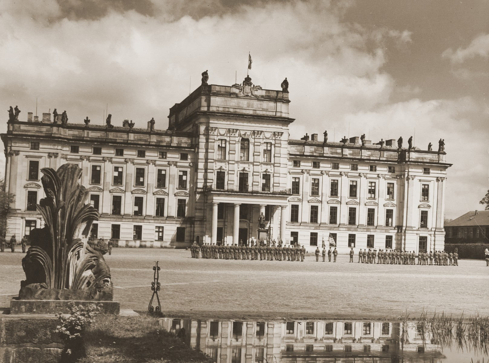 View of the palace and grounds of the Archduke of Mecklenburg, where the bodies of 200 prisoners from the nearby concentration camp of Woebbelin were buried by German civilians from Ludwigslust.  A sub-camp of Neuengamme, Woebbelin was captured by British and American troops on 4 May 1945.  Upon entering the camp, the liberators discovered nearly 4,000 prisoners, one-quarter of whom were already dead.  Outraged by what they found, the ranking Allied commanders in the area forced civilians from the nearby towns of Schwerin, Hagenow, and Ludwigslust to first see Woebbelin and then bury the bodies of prisoners in their towns.  The largest number of bodies, ca. 200, was buried in Ludwigslust on the palace grounds of the Archduke of Mecklenburg.  A slightly smaller number was buried in the garden of the leading Nazi official in Hagenow and 80 bodies were interred in Schwerin.  Every fourth grave was marked at each site with a Star of David in honor of the unidentified Jewish dead.