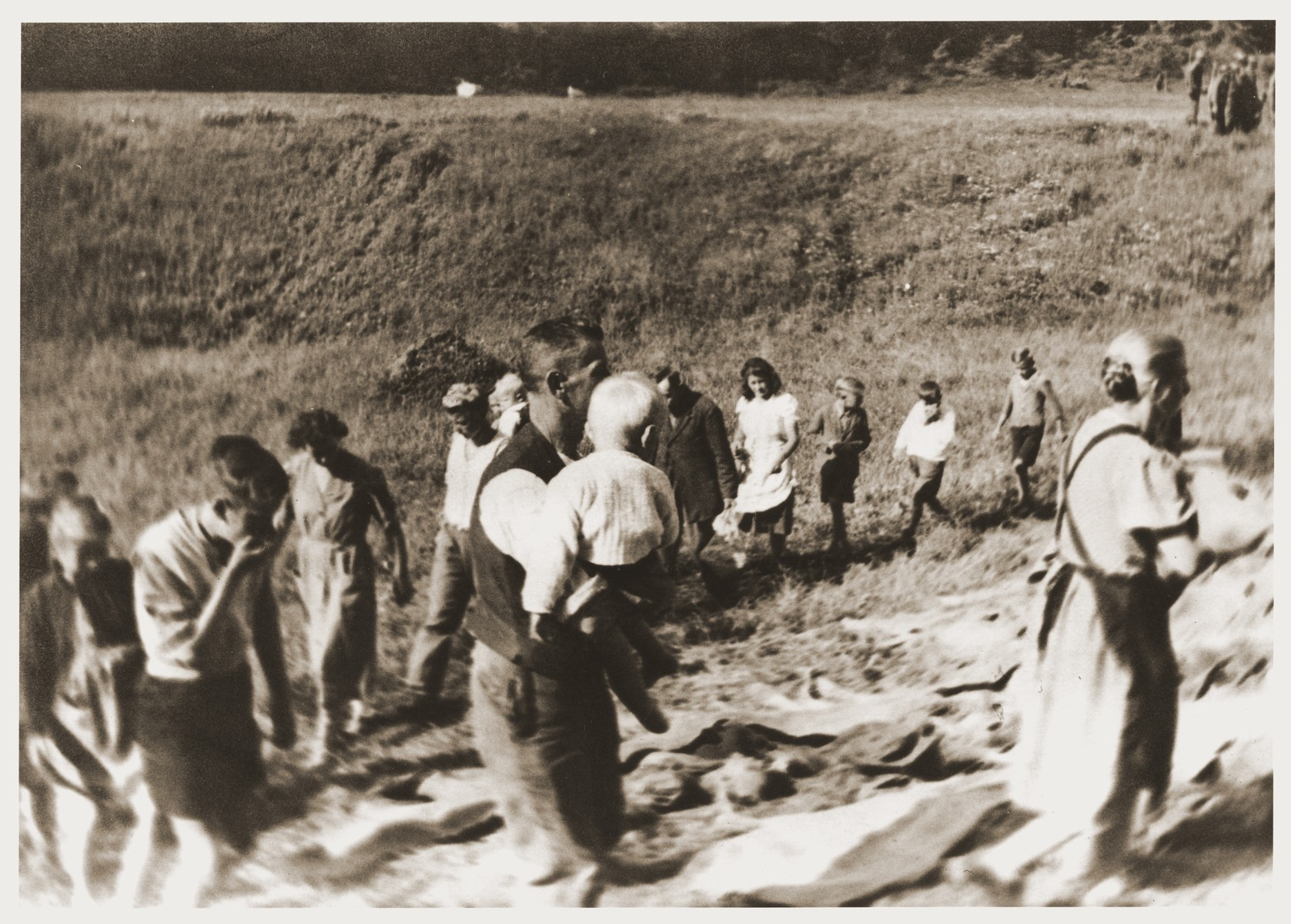 German civilians file past the exhumed bodies of former prisoners in Tittling, Germany.
