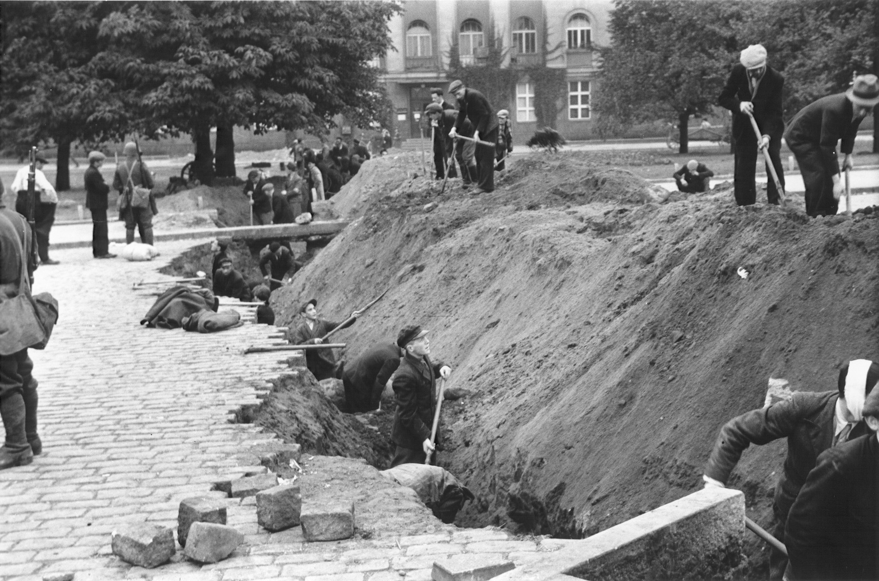 Polish civilians dig an anti-tank trench along a street in Warsaw to slow the advance of the German army.