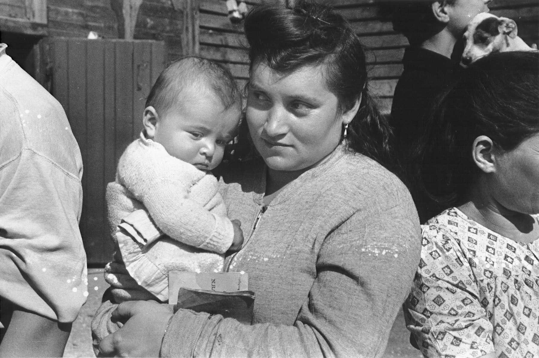 A Jewish DP mother holds her infant while waiting in line outside a barracks to register with IRO (International Refugee Organization) officials.