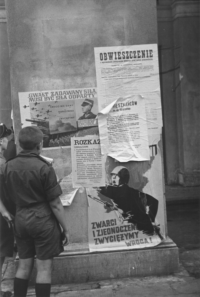 Two Polish boys read the posters and announcements that have been plastered on a pillar in Warsaw during the siege of the capital.