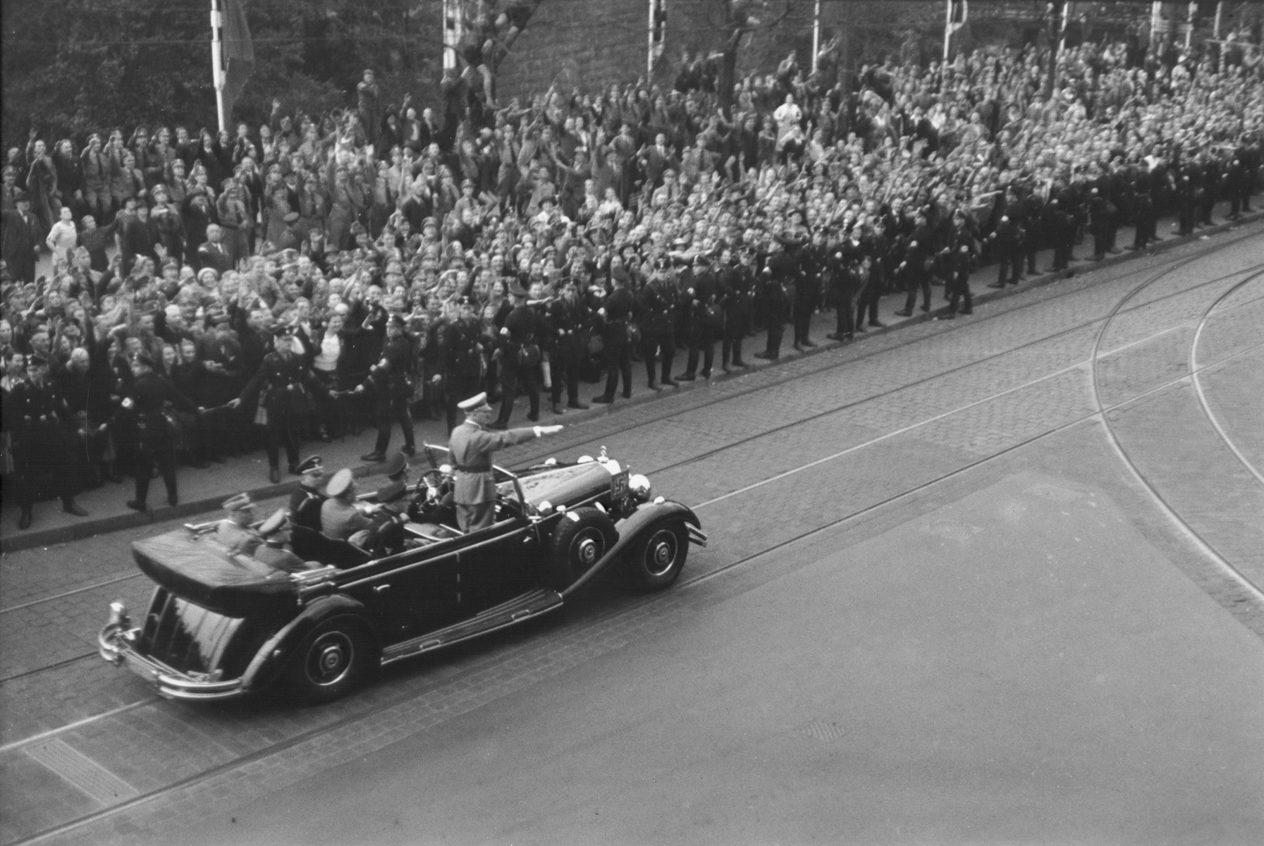 Standing in an open car, Adolf Hitler salutes the crowd that lines the street as he rides towards the hall where he will officially open the Great Anti-Bolshevism Exhibition 1937 (Grosse Antibolschewistische Ausstellung) in Nuremberg.